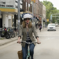 Woman confidently riding her bike downtown.