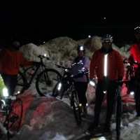 Winter bikers pose for a picture next to a snow bank.