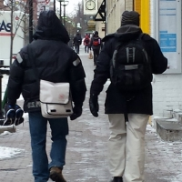 Two winter commuters walk down the street bundled up.